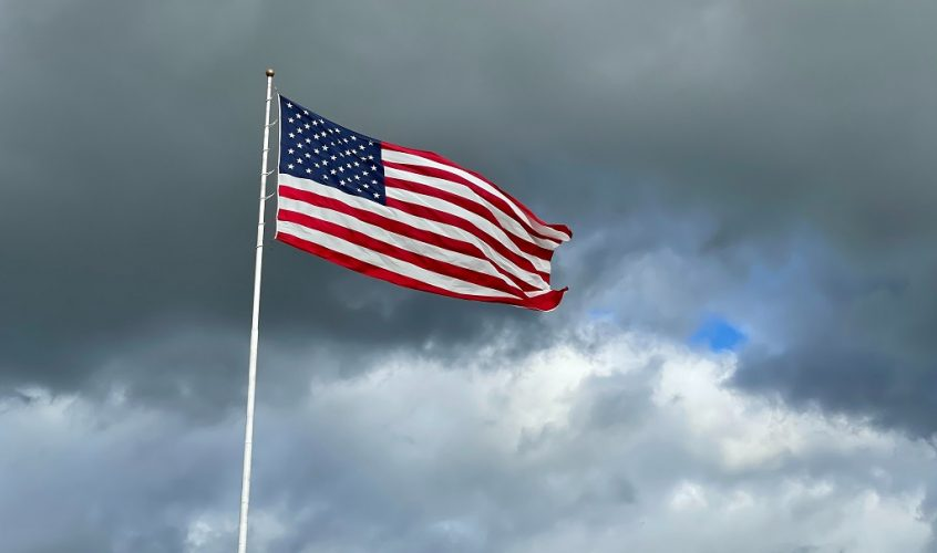 Us flag, dark clouds in the background