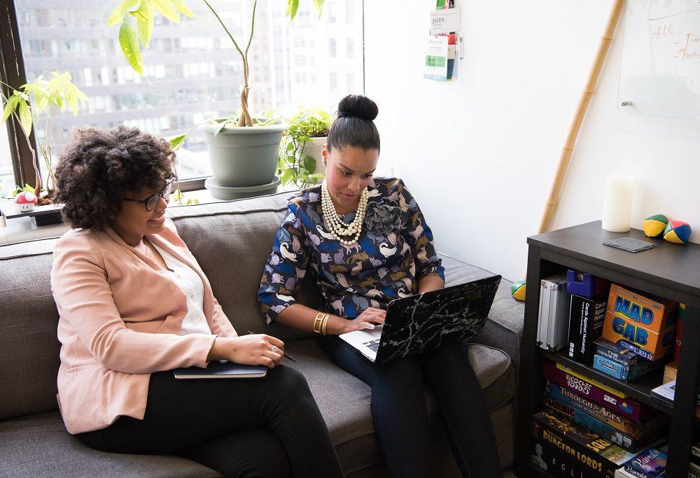 Women discussing something sitting on sofa